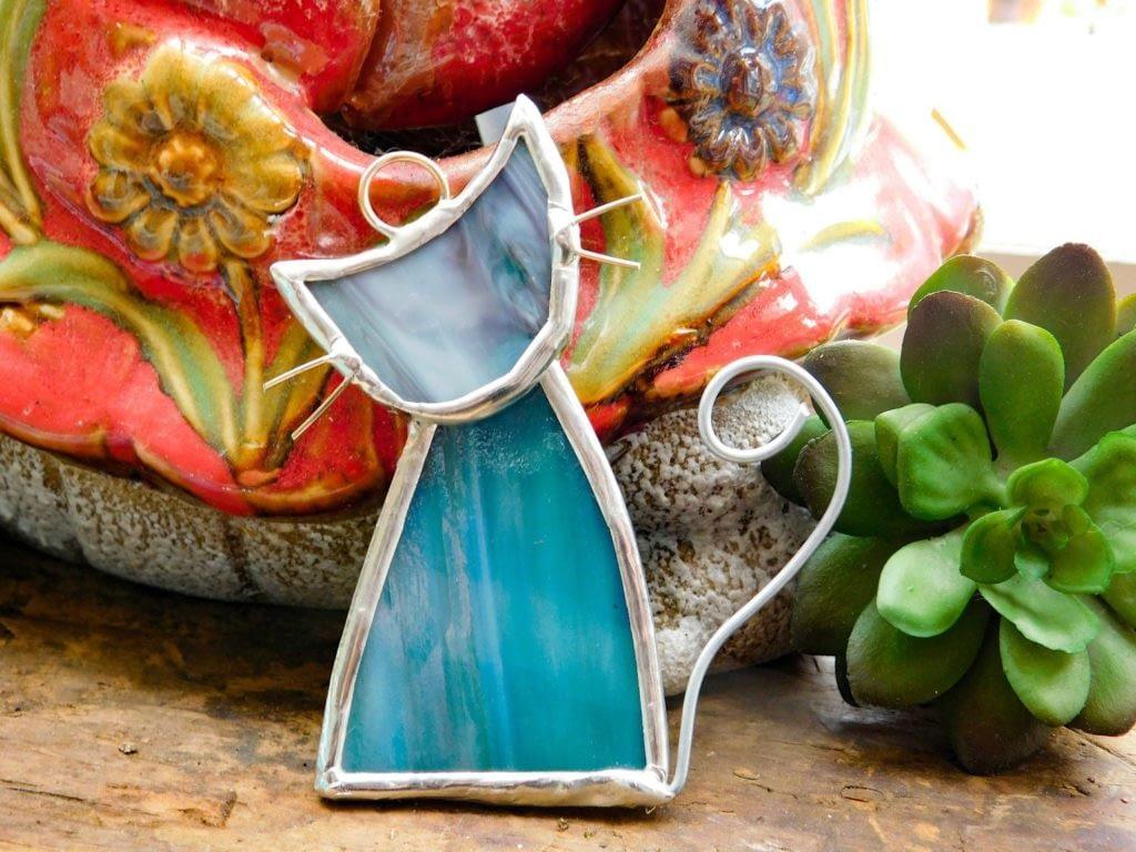 Aqua blue cat suncatcher ornament in front of succulent