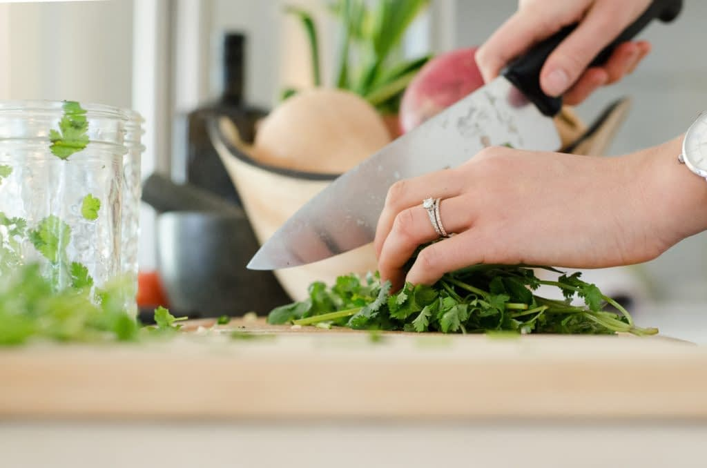 woman cutting vegetables on wooden cutting board