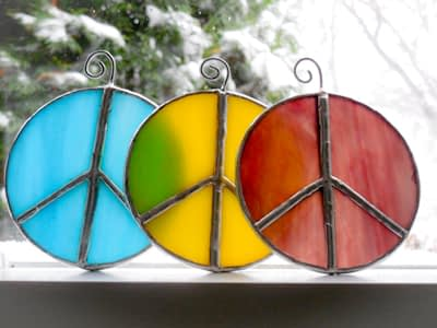 Stained glass peace sign suncatchers in a window.