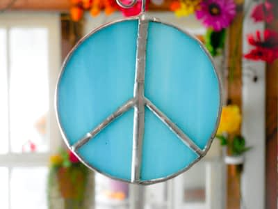 Aqua blue stained glass peace sign suncatcher with flowers in the background