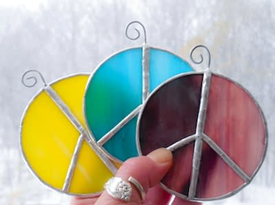 Hand holding three peace sign stained glass suncatchers in aqua, yellow and purple