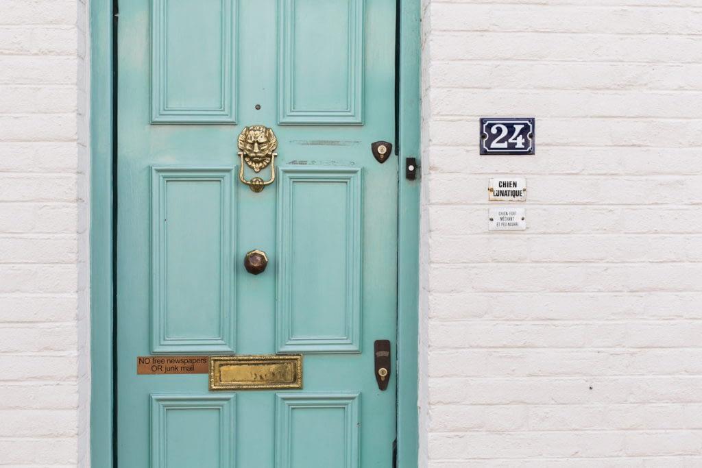 aqua door with brass knocker and doorknob