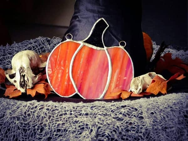 Orange stained glass pumpkin with witch hat and skulls