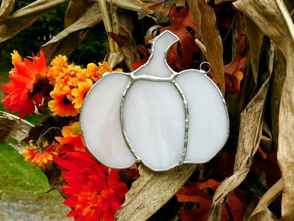 White stained glass pumpkin hanging in front of foddershock and mums